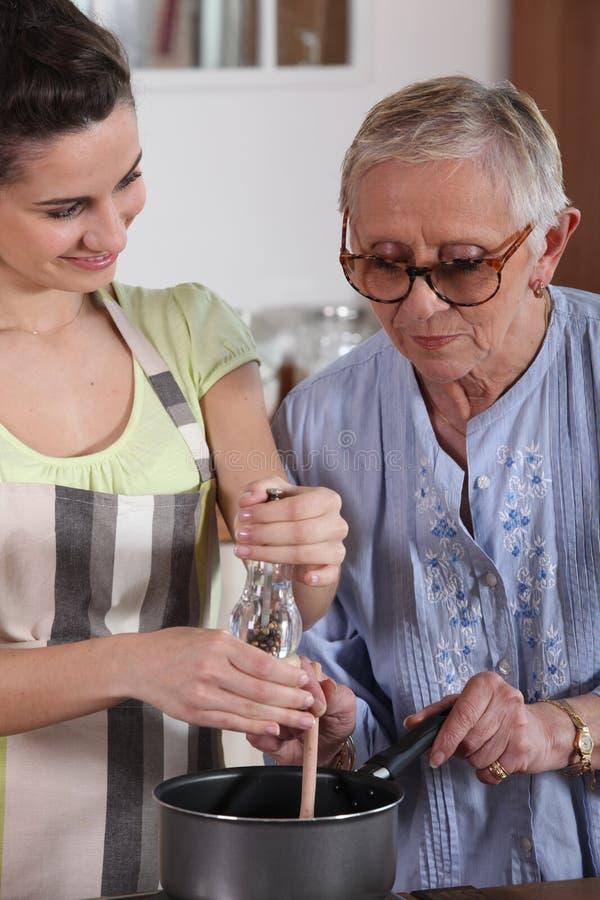 女孩和祖母烹调 免版税库存照片