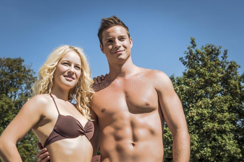 女孩和英俊的男孩佩带的游泳衣 库存照片