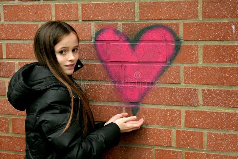 女孩和街道画心脏 免版税库存图片