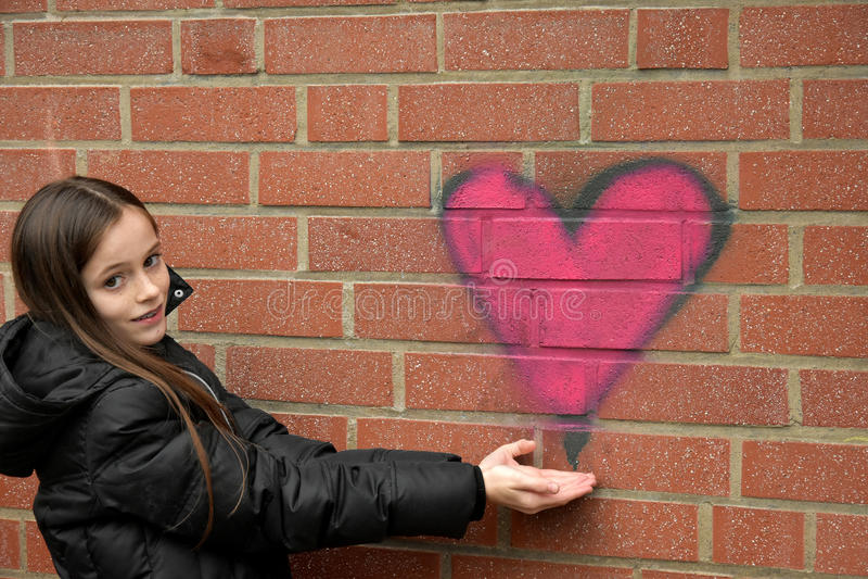 女孩和街道画心脏 库存照片