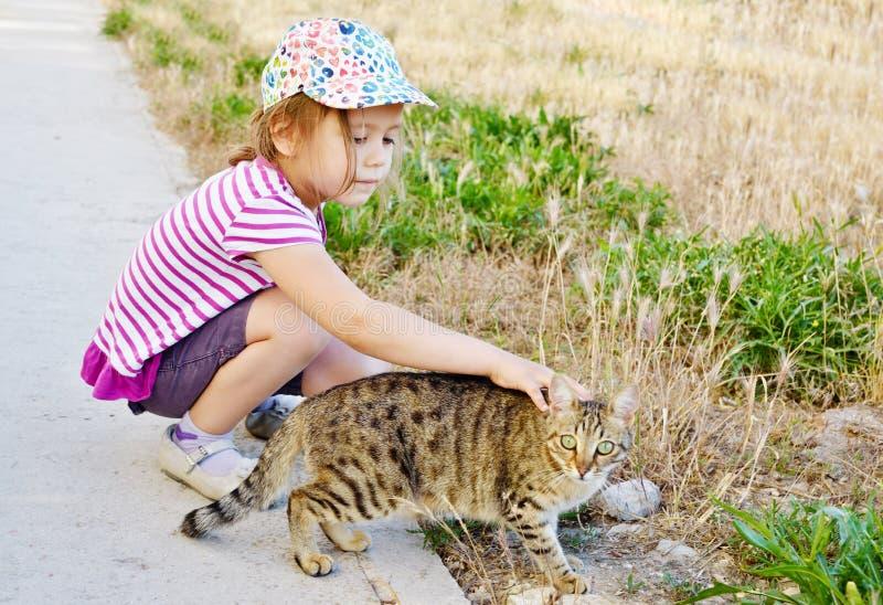 女孩和野猫 免版税图库摄影