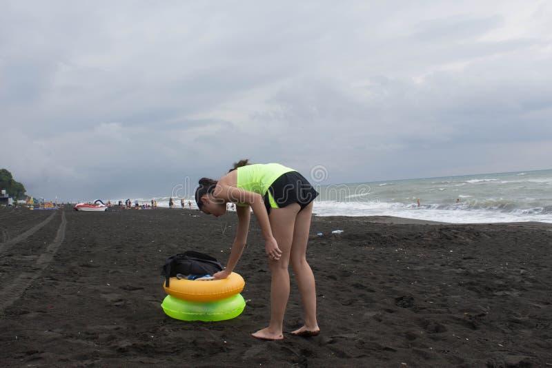 女孩和黄色,在海滩,阴云密布,云彩的绿色浮动圆环,挥动 免版税库存照片