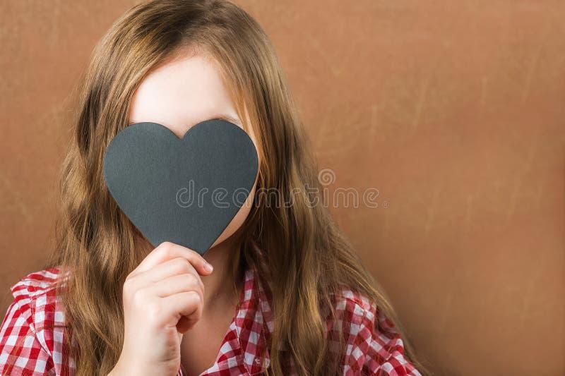 女孩和黑板岩心脏 女孩建立人相、鬼脸和心脏题字的 情人节概念,关闭 免版税库存图片