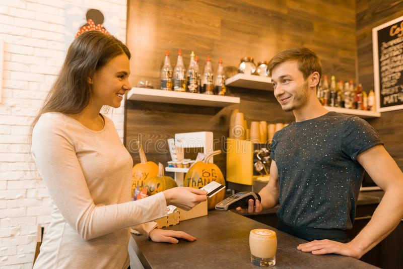 女孩咖啡馆客户由信用卡,拿着信用卡读者机器的barista支付咖啡 免版税图库摄影