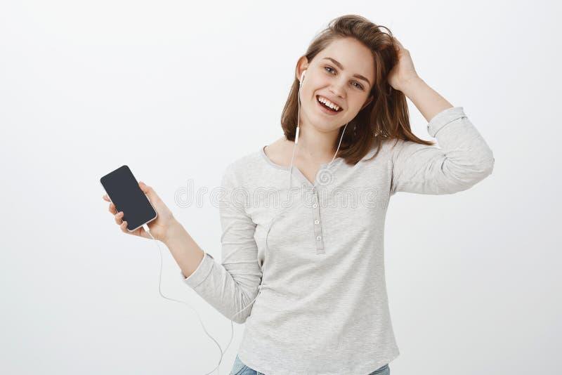 女孩喜欢与在耳朵的耳机一起使用 快乐的逗人喜爱的无忧无虑的欧洲轻轻地掀动头的女性感人的头发 免版税库存图片