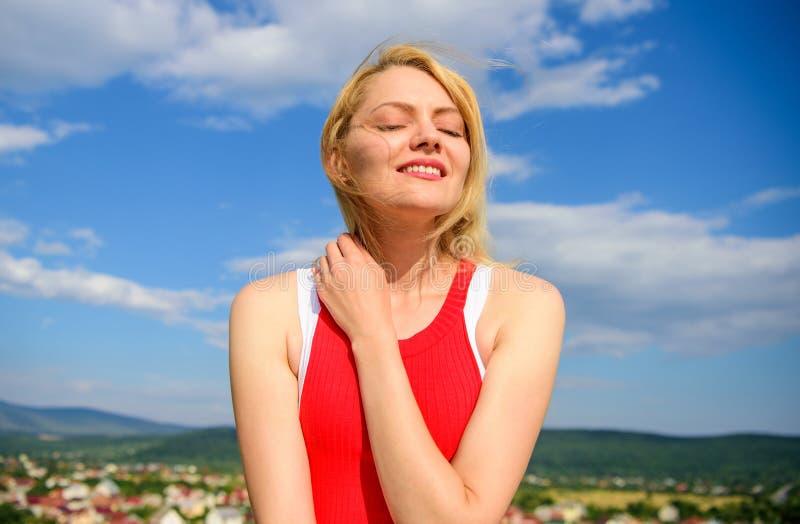 女孩喜欢与温暖的阳光看起来轻松的蓝天背景 妇女白肤金发放松户外 作为详细的关心 免版税图库摄影