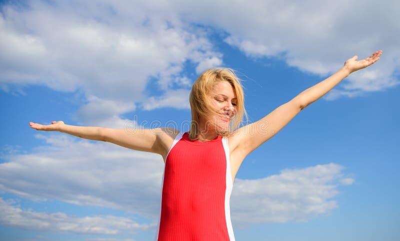 女孩喜欢与自由看起来轻松的无忧无虑的蓝天背景 感受和谐和和平 容易的作为 妇女金发碧眼的女人 库存图片