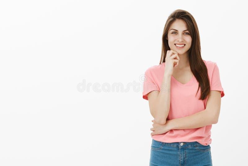 女孩喜欢听有趣的故事 桃红色T恤杉的愉快的无忧无虑和确信的女性工友,拿着棕榈 免版税库存照片