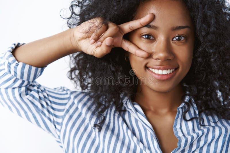 女孩喜欢显示和平标志的芳香树脂 画象感情无忧无虑的愉快的深色皮肤的年轻女人卷曲发型做迪斯科 免版税库存照片