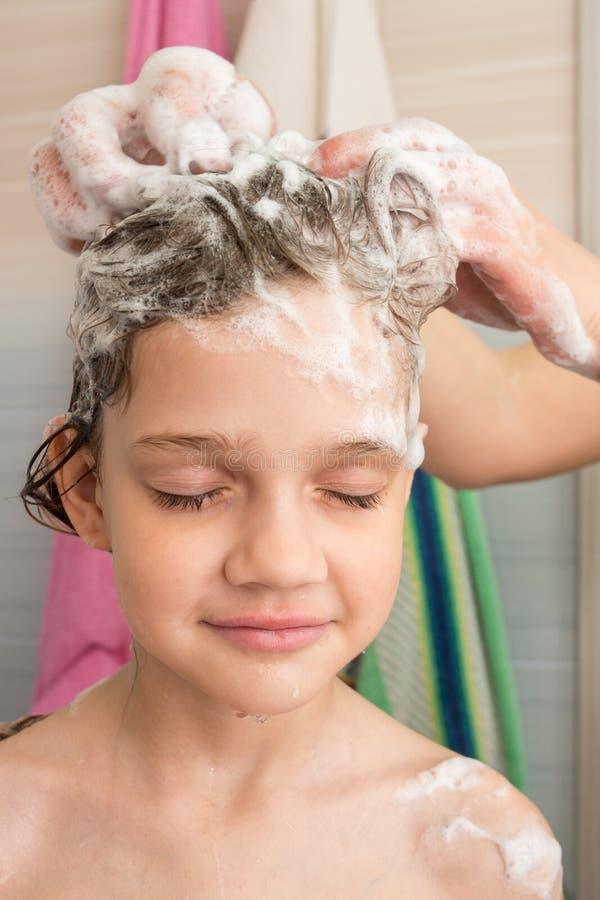 女孩喜欢,当妈妈香波她的头发 免版税库存图片