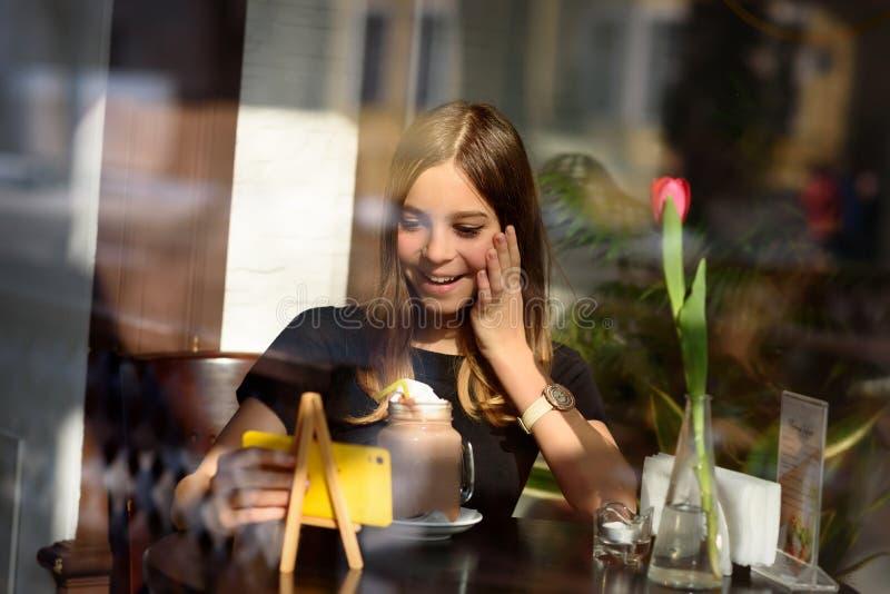 女孩喝咖啡并且观看在手机的录影 库存照片