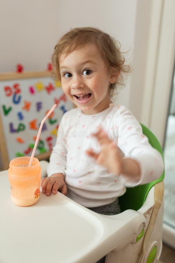 女孩喝温暖的牛奶坐在一把小儿童椅子的早餐 库存图片