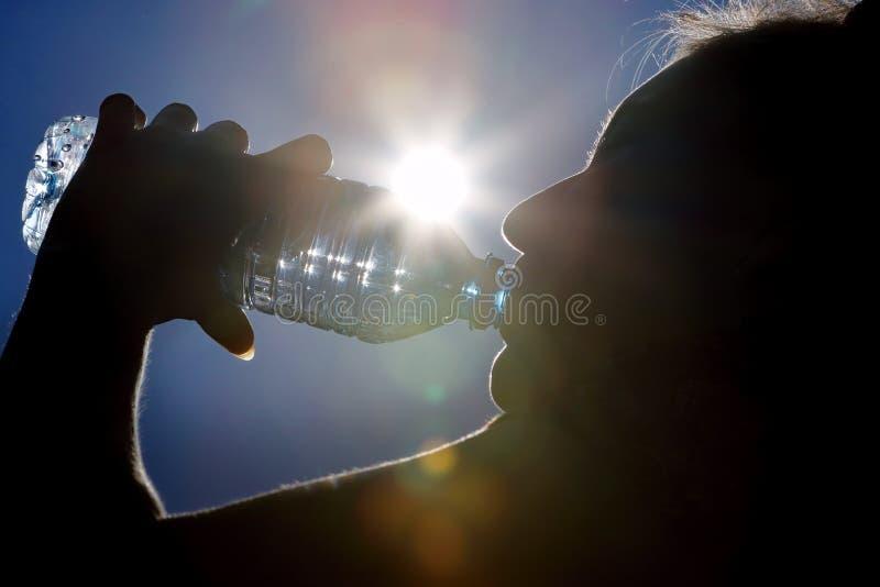 女孩喝从瓶在阳光下背景的水 库存图片