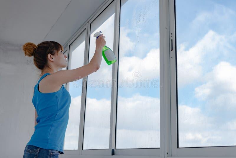 女孩喷洒洗涤的窗口的液体在肮脏的玻璃 免版税库存照片