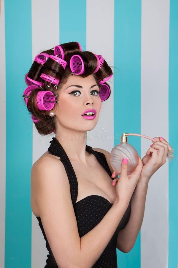 女孩喷洒的香水的减速火箭的别针与头发路辗 免版税图库摄影