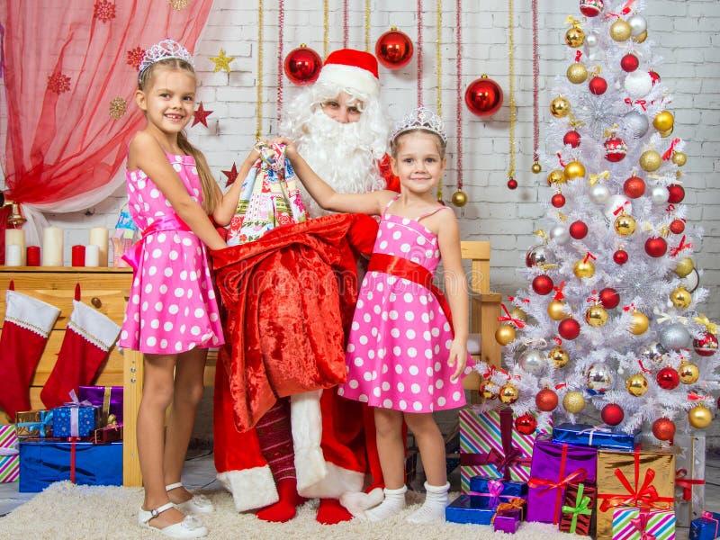 女孩圣诞老人圣诞节礼物拉出了袋子 库存照片