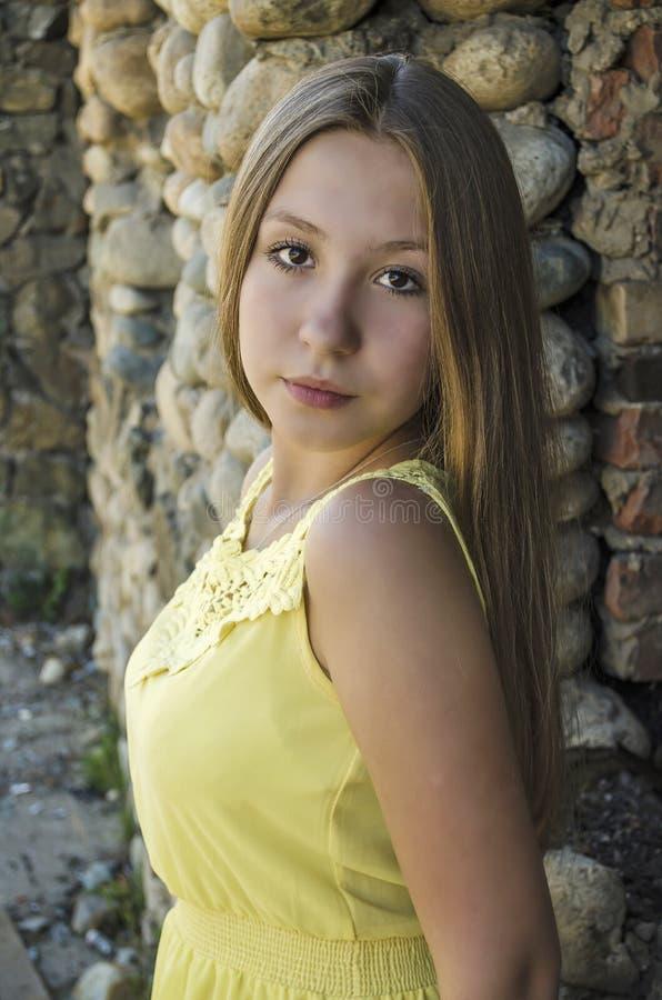 女孩在一个石墙附近站立 免版税库存照片