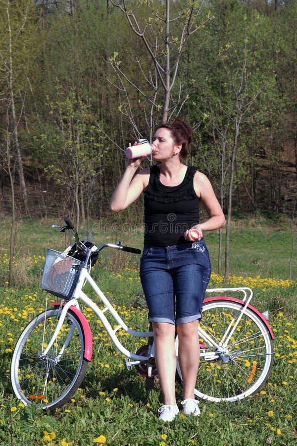 女孩在一辆停放的自行车倾斜 春天周期的基于 女孩喝从瓶的水 库存照片