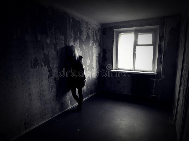 女孩在一间被放弃的蠕动的屋子 免版税库存照片
