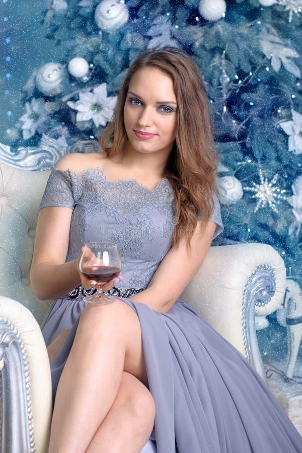 女孩在与一杯的一把椅子坐白兰地酒 免版税库存照片