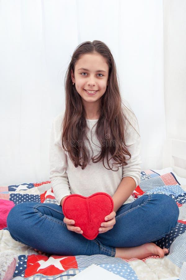 女孩在与与长毛绒心脏的床上坐 库存照片
