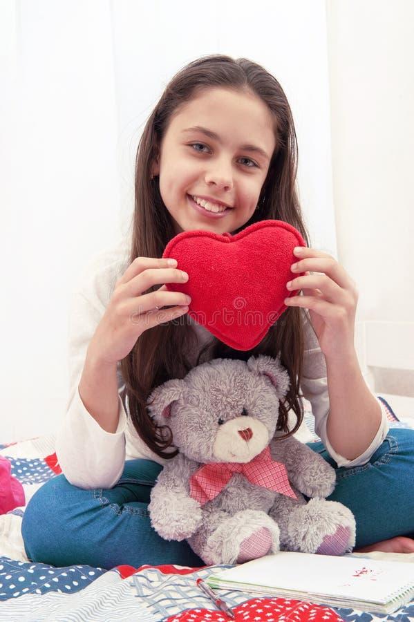 女孩在与与长毛绒心脏的床上坐 免版税库存图片