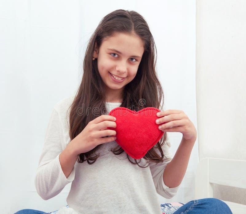女孩在与与长毛绒心脏的床上坐 免版税库存照片