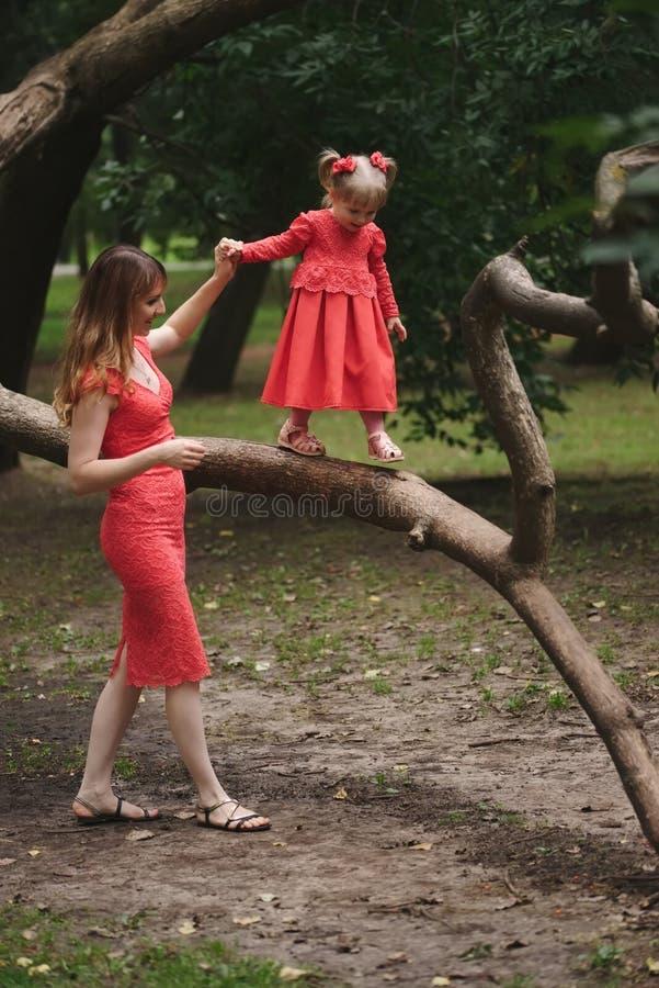女孩在与妈妈的树走 免版税图库摄影