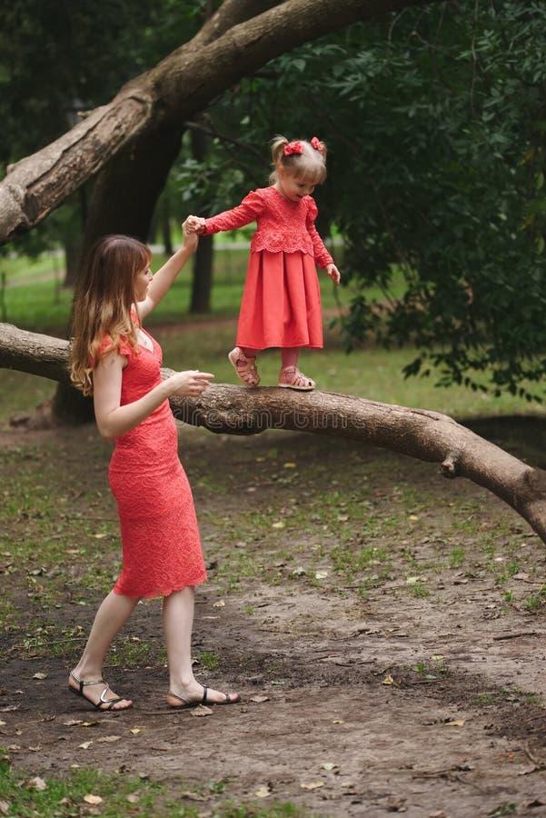 女孩在与妈妈的树走 免版税库存图片