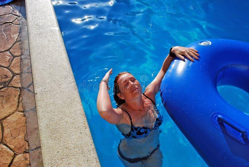 女孩在与橡胶环的水池游泳 她投掷了头并且漂洗头发 免版税库存照片