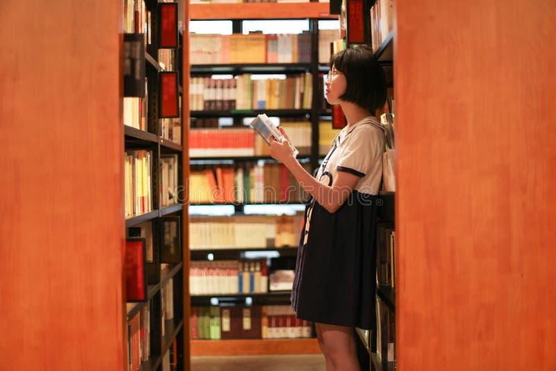 女孩在书店或图书馆 免版税图库摄影