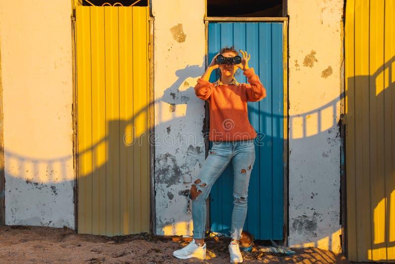 女孩在五颜六色的墙壁附近站立并且通过双筒望远镜看 免版税库存图片