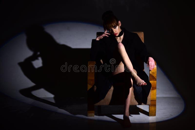 女孩在光的椅子坐黑暗的背景 秀丽和方式 看有时髦的头发的时髦妇女和 免版税库存照片