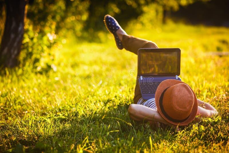 女孩在公园与膝上型计算机一起使用 图库摄影