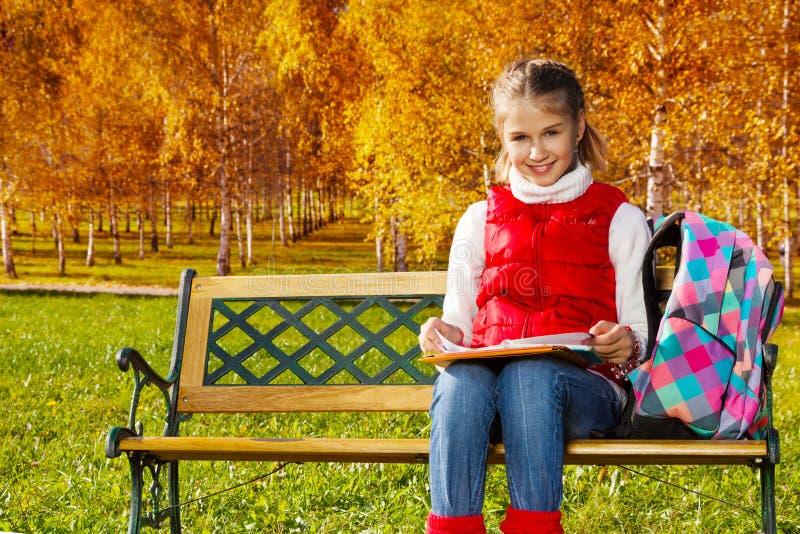 女孩在公园做家庭作业 库存图片