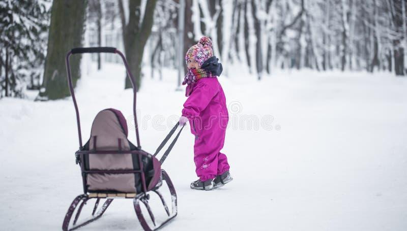 女孩在公园,一个独立孩子运载一个雪撬 库存照片