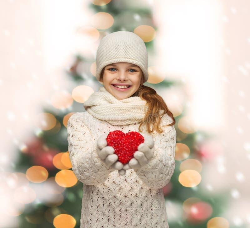 女孩在冬天穿衣与小红色心脏 库存照片