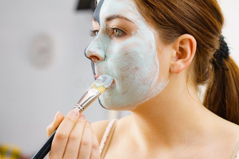 女孩在半面孔的黑色面具应用白色泥 库存图片