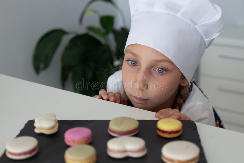 女孩在厨房里用板材蛋白杏仁饼干 免版税库存图片