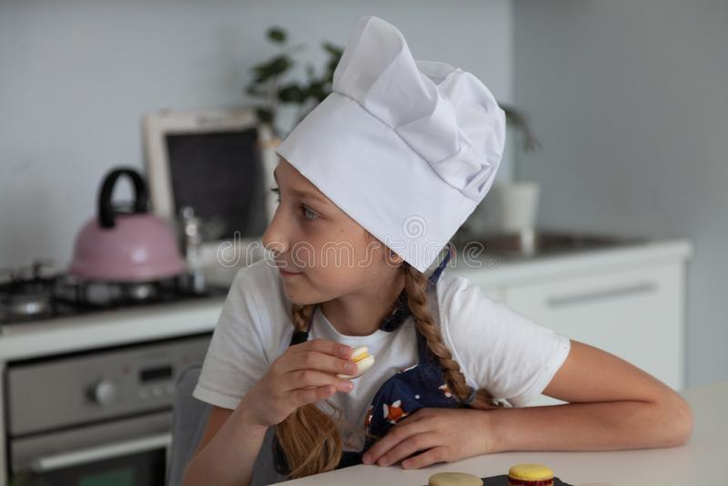 女孩在厨房里用板材蛋白杏仁饼干 库存照片