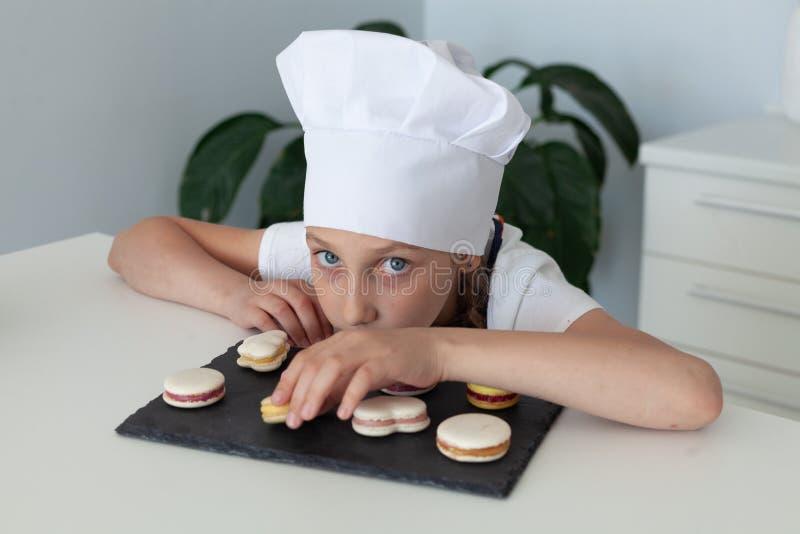 女孩在厨房里用板材蛋白杏仁饼干 免版税库存照片