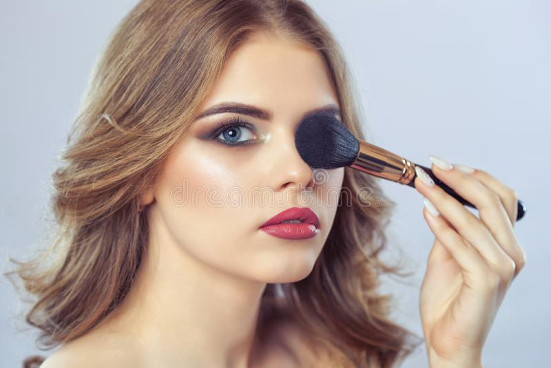 女孩在发廊绘在面孔的粉末,完成smokey眼睛化妆 库存图片