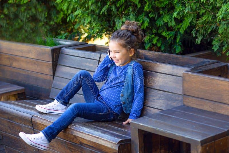 女孩在咖啡馆和微笑的电话谈话 Worki 免版税库存照片