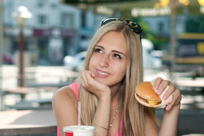 女孩在咖啡馆坐,吃汉堡和微笑户外 免版税库存图片