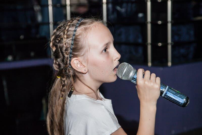 女孩在咖啡馆的唱歌卡拉OK演唱 免版税图库摄影