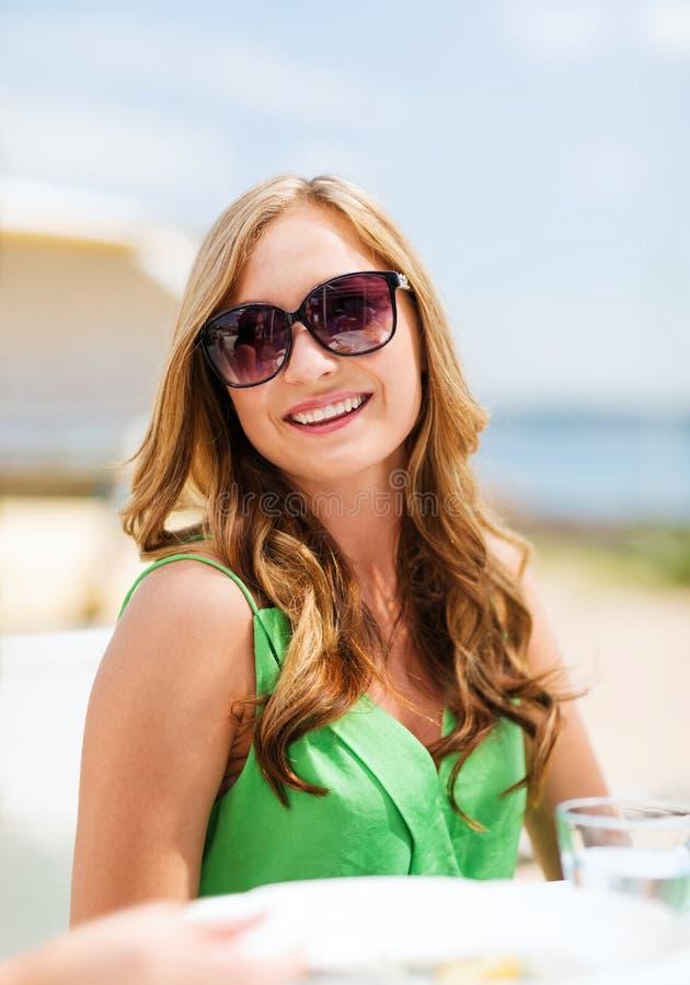 女孩在咖啡馆的树荫下在海滩 免版税图库摄影