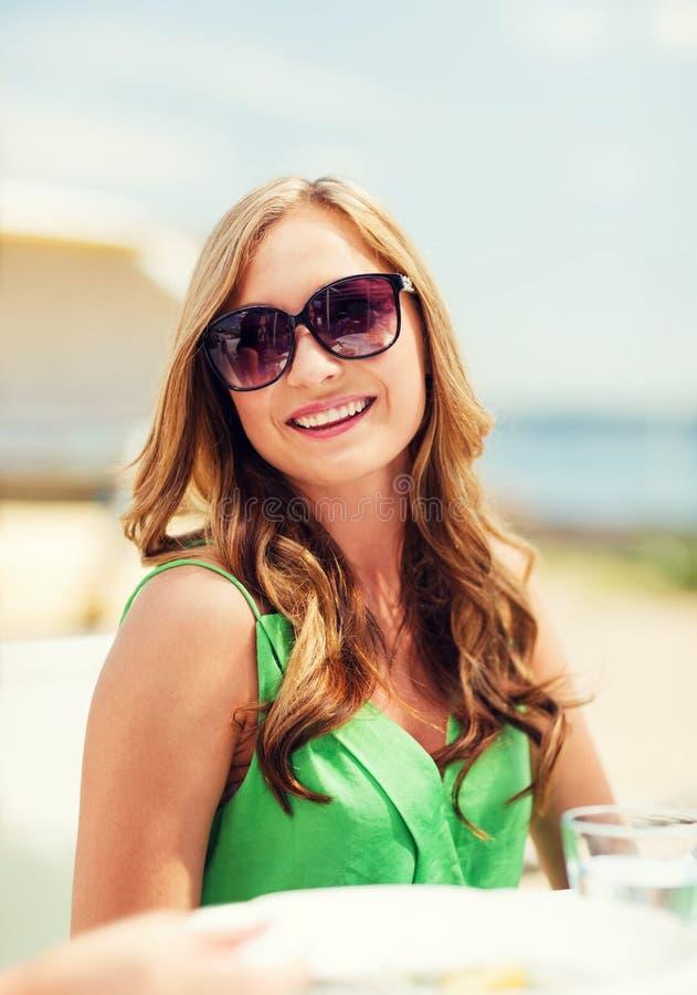 女孩在咖啡馆的树荫下在海滩 库存图片