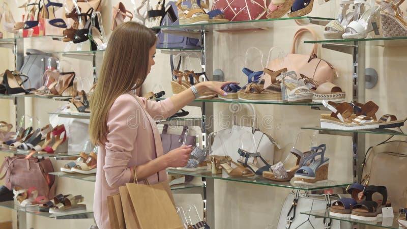 女孩在商店选择高跟鞋平台凉鞋 免版税库存照片