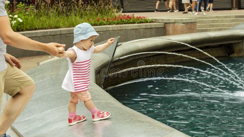 女孩在喷泉要游泳 婴孩去喷泉,拉扯他的手对水 帽子步行的欧洲女孩 免版税库存照片