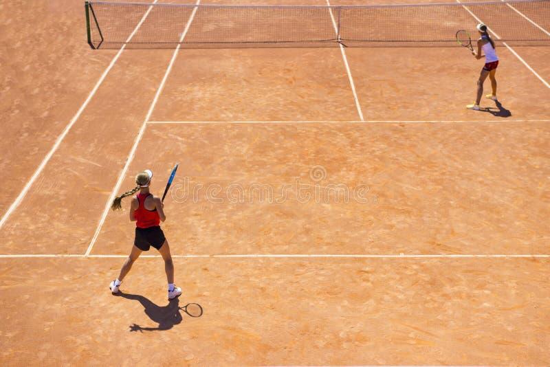 女孩在土法院的戏剧网球 网球被配对的比赛  新网球员 免版税库存照片